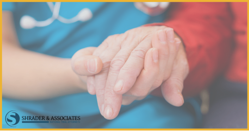 medical assistant holding elderly person's hand